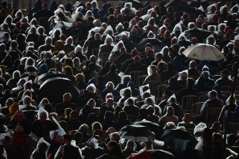 Religious people and faithfuls wear nylon raincoats as Pope Francis speaks during the welcoming ceremony offered to him by the youth for the World Youth Day ceremonies, at Rio de Janeiro's iconic Copacabana beachfront on July 25, 2013. (Gabriel Bouys/AFP/Getty Images)