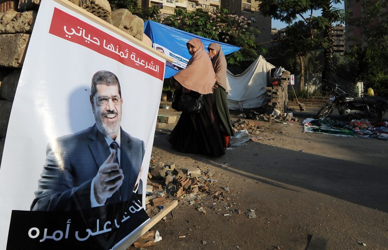 Egyptian women walk past a poster featuring deposed president Mohamed Morsi as his supporters continue to hold a sit-in outside Rabaa al-Adawiya mosque on July 25, 2013 in Cairo. Egypt's military and Mohamed Morsi's camp sought separately to defuse soaring tensions on the eve of rival rallies called by the army and Islamists who back the ousted president. (Fayez Nureldine/AFP/Getty Images)