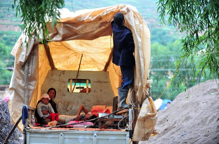 Earthquake-hit villagers living in a temporary tent on a truck in Minxian county in Dingxi, northwest China's Gansu province. At least 94 people were killed in the earthquake, China's official news agency reported, citing local authorities, with 1,000 more injured and 51,800 homes collapsed. (STR/AFP/Getty Images)