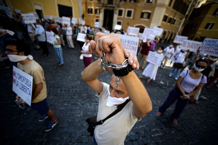 A demonstrators show his chained hands as he stands in front of the Italian parliament with other people with their mouths and hands tied to protest against homophobia in Rome's Piazza Montecitorio on July 26, 2013. Italy's lower house of Parliament began debating Tuesday a bill that would make homophobia a criminal offense. The law is considered very controversial as the Catholic Church considers homosexuality a sin and as several Catholic figures spanning across center-left and center-right fear the bill could curtain freedom of speech and opinion. (Filippo Monteforte/AFP/Getty Images)