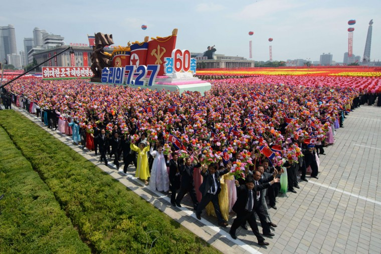 North Koreans wave flowers as they take part in a military parade past Kim Il-Sung Square marking the 60th anniversary of the Korean war armistice in Pyongyang on July 27, 2013. North Korea mounted its largest ever military parade on July 27 to mark the 60th anniversary of the armistice that ended fighting in the Korean War, displaying its long-range missiles at a ceremony presided over by leader Kim Jong-un. (Ed Jones/AFP/Getty Images)