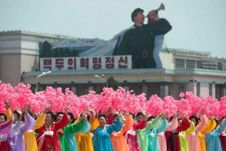 North Korean women wearing traditional dress wave flowers as they stand on Kim Il-sung Square during a parade marking the 60th anniversary of the Korean war armistice in Pyongyang on July 27, 2013. North Korea mounted its largest ever military parade on July 27 to mark the 60th anniversary of the armistice that ended fighting in the Korean War, displaying its long-range missiles at a ceremony presided over by leader Kim Jong-un. (Ed Jones/AFP/Getty Images)