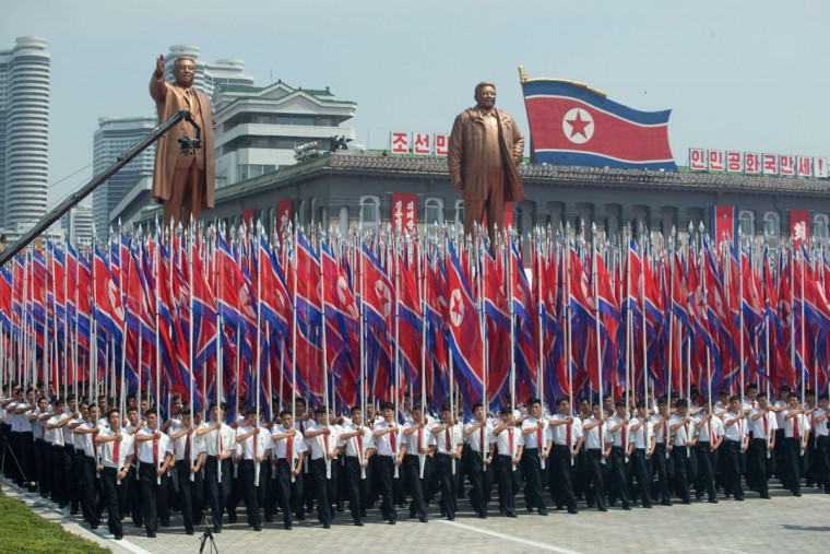 North Koreans wave flags and walk with statues of former leaders Kim Il-sung and Kim Jong-il during a military parade past Kim Il-sung Square marking the 60th anniversary of the Korean war armistice in Pyongyang on July 27, 2013. North Korea mounted its largest ever military parade on July 27 to mark the 60th anniversary of the armistice that ended fighting in the Korean War, displaying its long-range missiles at a ceremony presided over by leader Kim Jong-un. (Ed Jones/AFP/Getty Images)