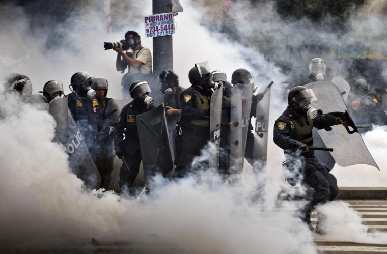 Riot policemen stand in a tear gas cloud during clashes within a student and workers protest against the government, in Lima on July 27, 2013. Students protested against a bill -- that if passed -- would reduce university autonomy, whilst workers did it against a new civil service law which could bring massive dismissals, according to the workers' union. (Ernesto Benavides/AFP/Getty Images)