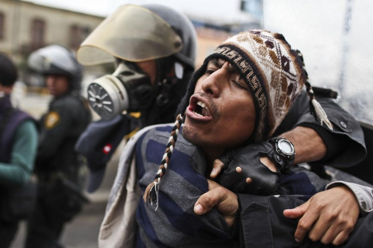 A demonstrator is arrested by the police during a students and workers protest against the government, in Lima on July 27, 2013. Students protested against a bill -- that if passed -- would reduce university autonomy, whilst workers did it against a new civil service law which could bring massive dismissals, according to the workers' union. (Ernesto Benavides/AFP/Getty Images)