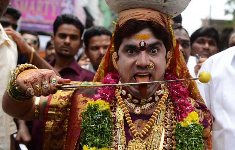 An Indian Hindu male devotee dressed as a women carries 'ghatam', a pot filled with cooked rice and decorated with neem leaves, during the festival of Bonalu, a ritual offering to the goddess Kali, at the Sri Ujjaini Mahakali Temple on July 28, 2013. The Goddess Kali is honored mostly by women during Bonalu festival with offerings of food and dancing. (Noah Seelam/AFP/Getty Images)