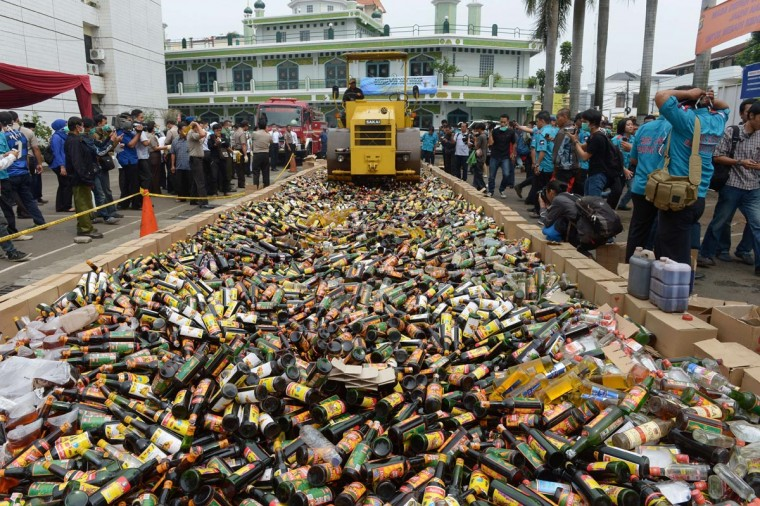 A worker uses a steamroller to crush thousands bottles of alcoholic drinks as part of a police operation during Ramadan at South Jakarta police headquarters in Jakarta on July 29, 2013. About 10,681 alcohol drinks, mostly local made were destroyed by police after they were seized from vendors who failed to show documents permitting their sale. (Adek Berry/AFP/Getty Images)