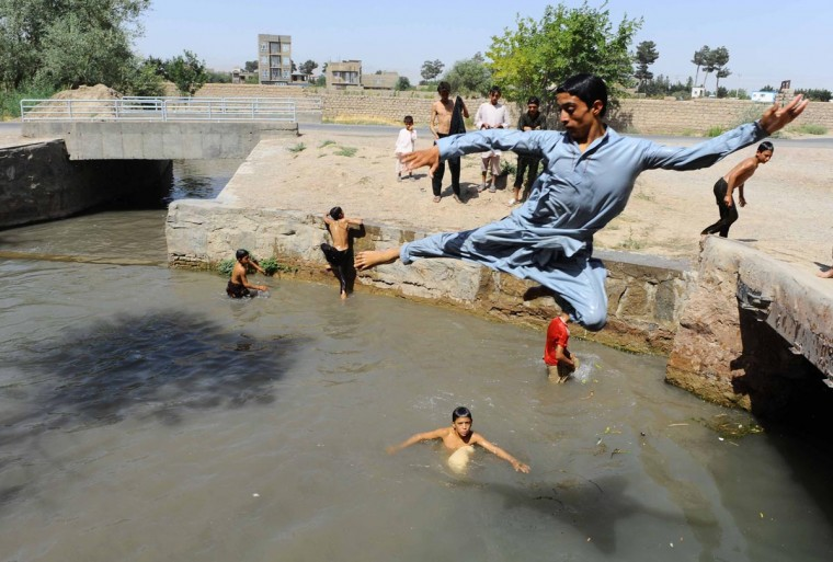 Afghan young men cool off at a river in Herat on July 29, 2013. Western Afghanistan is flat and open with the climate accordingly hot and dry around Herat and temperatures are reaching the early forties. (Aref Karimi/AFP/Getty Images)