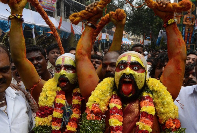 Indian Hindu devotees representing Potharaju, brother of the goddess Mahankali, dance in the streets during the Bonalu festival at the Sri Ujjaini Mahakali Temple in Secunderabad, the twin city of Hyderabad, on July 29, 2013. The Goddess Kali is honored mostly by women during Bonalu festival by offerings of food and dancing. (Noah Seelam/AFP/Getty Images)