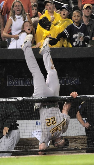 The Oakland Athletics' Jack Hannahan goes up and over the dugout railing in pursuit of Orioles hitter Luke Scott's foul ball in the fifth inning of a baseball game, September 2008 in Baltimore. Hannahan was able to hang on to the ball for the out. (Gene Sweeney Jr./Baltimore Sun)