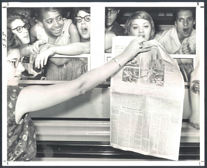 July 6, 1963: Demonstrators, held in a school bus while awaiting court appearances at Woodlawn last night, examine a newspaper account of their demonstration and arrests at Gwynn Oak Park. They were allowed to go free pending trial. (Richard Childress/Baltimore Sun)