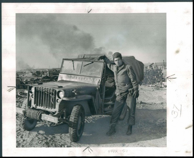 "Published January 1951: Private Bernard C. Bruettner, of 43 North Janney street, Baltimore, had his litter jeep, ""The Maryland Kid,"" on the beach. (James M. Cannon/Baltimore Sun)"