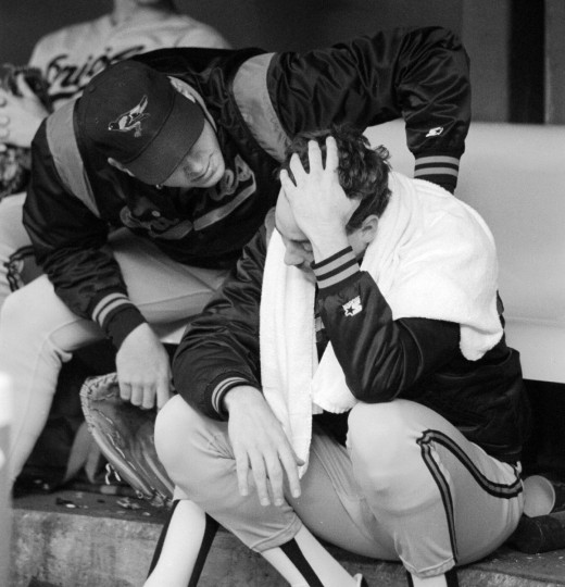 "At the next-to-last game of the Orioles' magical 1989 ""Why Not' season, Orioles starting pitcher Dave Johnson (who was an emergency fill-in when starter Pete Harnish stepped on a nail) is consoled by Bob Milacki after the O's lost 4-3 to the Blue Jays and lost a shot at the American League East pennant., on September 29, 1989 in Toronto. The Orioles went to Toronto needing a three-game sweep in order to take the pennant and make the playoffs. Johnson left the game in the eighth inning having pitched the game of his life, giving the Orioles a 3-1 lead, only to watch the bullpen lose the game. (Gene Sweeney Jr./Baltimore Sun)"