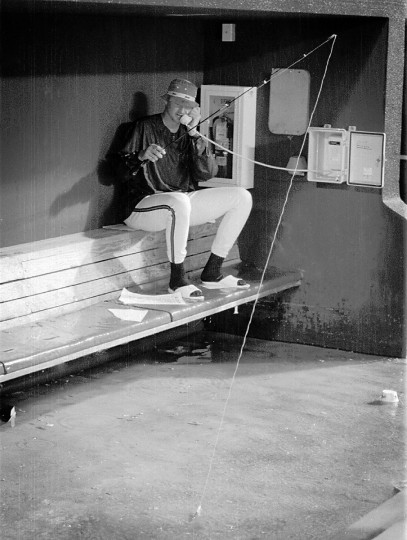 Orioles pitcher Ben McDonald took the monsoon rain in stride during the delay at Oriole Park in Camden Yards in June 1993. McDonald brought out his rod and reel to try and see what he might catch in the O's dugout, which was flooded due to heavy rains. (Gene Sweeney Jr./Baltimore Sun)