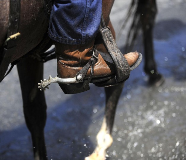 One of the saltwater cowboys sports cowboy boots complete with spurs as he helps herd the ponies through the town and to the carnival grounds. (Erin Kirkland/Baltimore Sun)