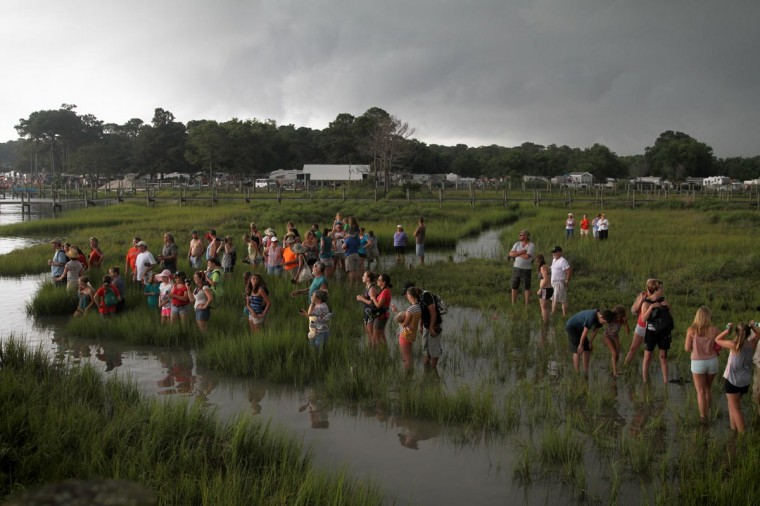 Those not scared away by the storm, wait in knee-deep water for the ponies to swim across at the annual Chincoteague Pony Swim. The Chincoteague Volunteer Firefighter Company herds wild ponies from Assateague Island to Chincoteague Island, where they are auctioned off the following day. (Erin Kirkland/Baltimore Sun)