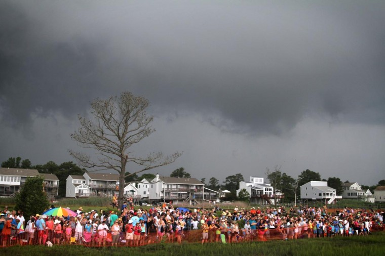 Those not scared away by the storm that rolled in, wait for the ponies to swim across at the annual Chincoteague Pony Swim. (Erin Kirkland/Baltimore Sun)