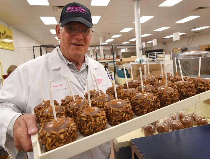 Paul Wockenfuss, president and third generation family owner of Wockenfuss Candies, he holds a tray of Monster Pecan Apples.
