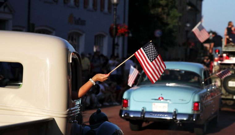 A participant of the Annapolis Fourth of July Parade waves an American flag. (Erin Kirkland/Baltimore Sun)