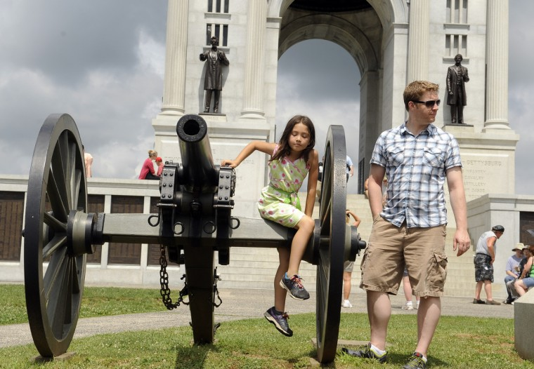 Lorelai Jenkins, 8, climbs on a cannon as her dad Chris Jenkins stands on right at the 150th anniversary of the Battle of Gettysburg. They are from Elkridge. (Barbara Haddock Taylor/Baltimore Sun)