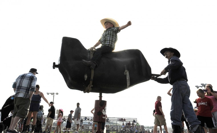 Michael Wynkoop, 5, of Smithsburg, Md. rides a mechanical bull with the help of professional bull rider Robert Carter, right. (Lloyd Fox/Baltimore Sun)