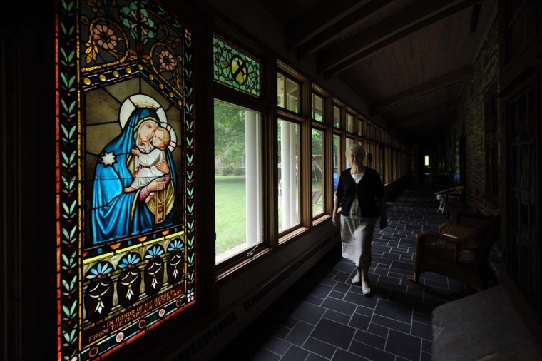 Sister Constance (Connie) FitzGerald walks by a stained glass window of Our Lady of Mount Carmel. The window was moved from the old monastery on Biddle Street to Baltimore Carmel's current location in Towson. A date on the window reads Oct. 15, 1897. (Kim Hairston/Baltimore Sun)