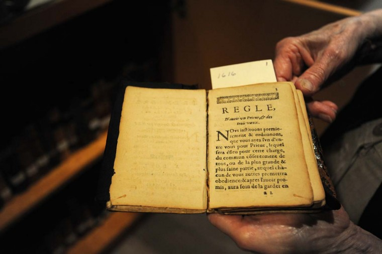 Sister Constance (Connie) FitzGerald holds the Rule of Albert, a book from 1616, which outlines how to live a Christian life. The book is in the Carmelite Monastery archives. (Kim Hairston/Baltimore Sun Photo)