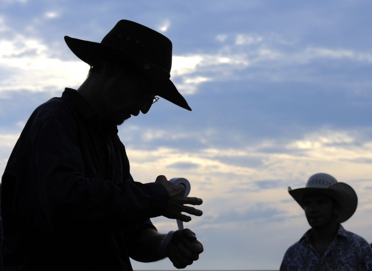 Robert Carter wraps tape around his wrists as he prepares for the bull riding competition. (Lloyd Fox/Baltimore Sun)