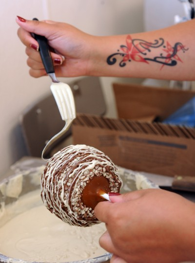 Christina Rucker decorates caramel-dipped apples with strings of brown and white chocolate. (Algerina Perna/Baltimore Sun)