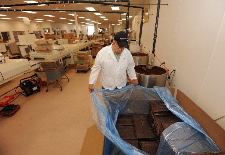 Paul Wockenfuss, president and owner of Wockenfuss Candies, looks at a box of Peter's Chocolate from Lititz, Pa. The box in the foreground right holds 1800 pounds of chocolate. (Algerina Perna/Baltimore Sun)