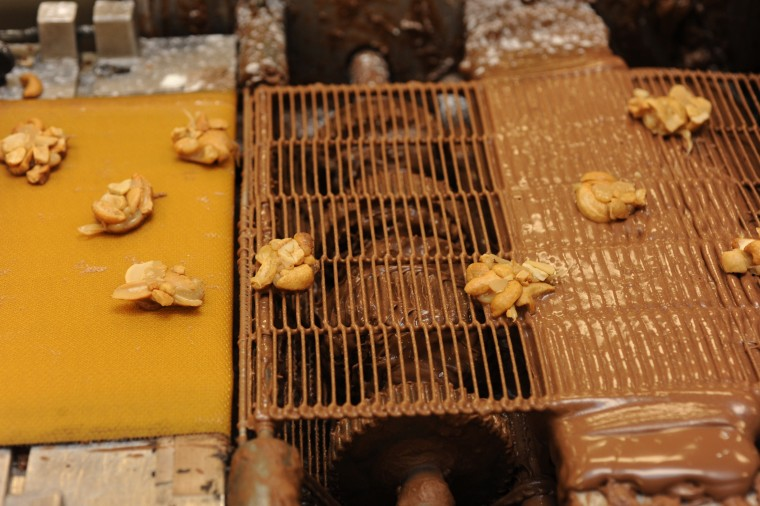 Nuts with caramel move on a conveyor belt on their way to be dipped in chocolate. (Algerina Perna/Baltimore Sun)