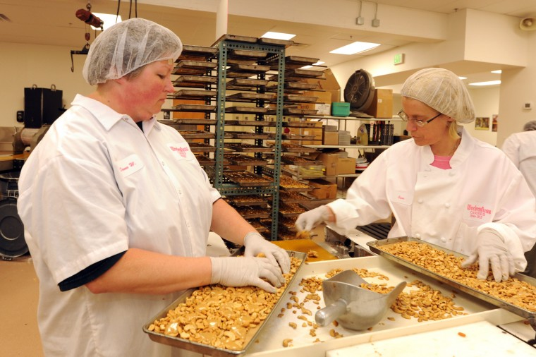 Donna Winters, left, and Jean Anderson, production workers, break off the excess cashew nuts with caramel before they will be covered in chocolate. (Algerina Perna/Baltimore Sun)