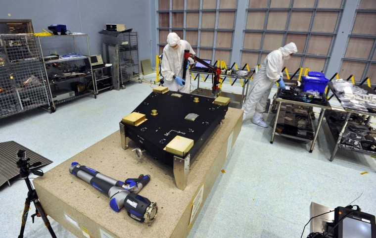 Contractors examine equipment recently delivered to the clean room at NASA Goddard Space Flight Center. In the foreground on the table are precision measuring devices. (Algerina Perna/Baltimore Sun)