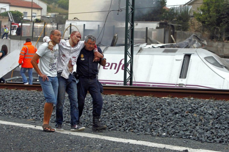 Rescue workers help a victim of a train crash near Santiago de Compostela, northwestern Spain, July 24, 2013. At least 56 people died after a train derailed in the outskirts of the northern Spanish city of Santiago de Compostela, the head of Spain's Galicia region, Alberto Nunez Feijoo, told Television de Galicia. (REUTERS/Monica Ferreiros/La Voz de Galicia)