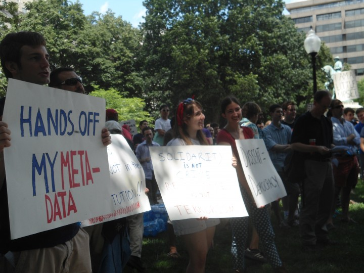 A group holds signs at an the DC pro-4th-ammendment demonstration on Independence Day. Group members include (from left) Ross Mattheis of California, Renaldo Lobato of Denver and Sonia Gonzalez of Los Angeles.