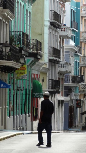 A pedestrian crosses over Calle San Francisco (San Francisco Street) in Old San Juan. The primary architectural influence in the colonial-era buildings is Spanish, much like areas of New Orleans in the United States. (Robert K. Hamilton/Baltimore Sun)