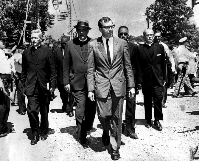 July 4, 1963: Clergymen of varied faiths head for a patrol wagon at Gwynn Oak Park during anti-segregation demonstrations. They included the Rev. Joseph M. Connolly of the Catholic Interracial Council (left), the Rev. Dr. Eugene Carson Blake, stated clerk of the United Presbyterian Church (second to left), and the Rev. Marion C. Bascom, pastor of Douglas Memorial Church (fourth from left). Some 283 persons were arrested at the amusement park. (Clarence B. Garrett/Baltimore Sun)