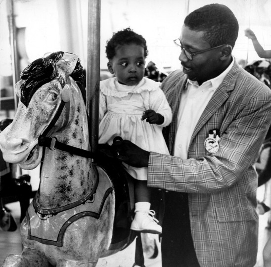 Aug 28, 1963: Sharon Langley, 11 months, becomes the first African American child to ride the Gwynn Oak Park carousel with help from father Charles Langley. (William L. La Force, Jr./Baltimore Sun)