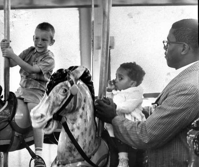 August 28, 1963: Sharon Langley keeps a firm grip on her thumb as she bobs up and down on the merry-go-round at Gywnn Oak Park, the first member of her race to ride the devices at the amusement park. Holding her is her father, Charles Langley. (William L. La Force, Jr./Baltimore Sun)