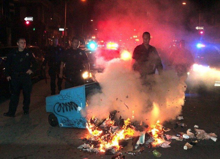 Oakland police extinguish a fire in Oakland, California, Sunday, July 14, 2013. Protesters became destructive after learning that George Zimmerman was found not guilty in the shooting death of Trayvon Martin. (Anda Chu/Bay Area News Group/MCT)