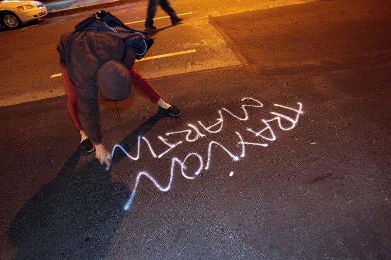A woman spray paints Trayvon Martin's name in Oakland, California, Sunday, July 14, 2013, after learning that George Zimmerman was found not guilty in the shooting death of Trayvon Martin. (Anda Chu/Bay Area News Group/MCT)