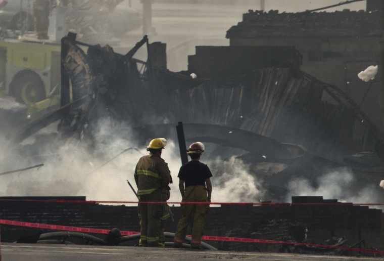 Firemen looked at the smoldering remains of a derailed train, Sunday, July 7, 2013, in Lac-Megantic, Quebec, Canada. The train carrying crude oil derailed Saturday in the middle of the Quebec town of Lac-Megantic, triggering a series of explosions and fire that killed at least one person and obliterated the city center. (Lucas Oleniuk/Toronto Star/Zuma Press/MCT)