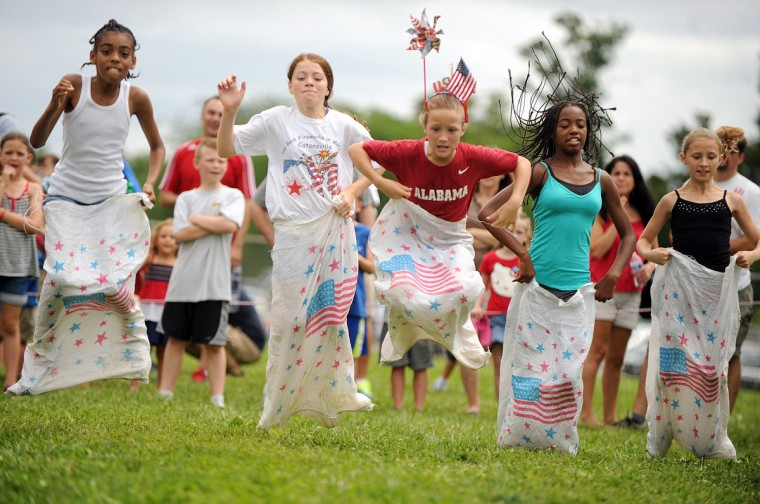 Wearing a pinwheel and American flag on her head, Cecelia Pell, 10, of Catonsville bounces her way to victory amongst other contestants in a sack race during the annual Independence Day games at Catonsville High School. (Brian Krista/Baltimore Sun Media Group)