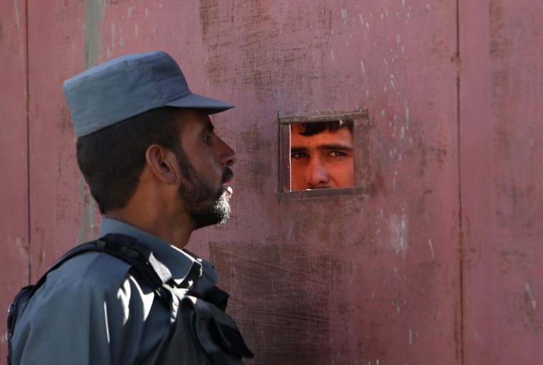 An Afghan policeman talks to a civilian standing behind a door near the site of a suicide attack in Kabul July 2, 2013. Taliban insurgents including a suicide bomber in a truck killed six people in the attack on a foreign logistics and supply company in Kabul on Tuesday. (Mohammad Ismail/Reuters)