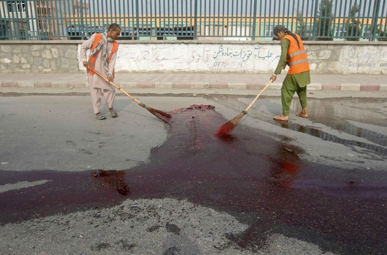 Afghan municipality workers remove blood from a site of an explosion in Jalalabad province, July 16, 2013. A bomb planted on a bicycle detonated on Tuesday killing at least two people and injuring three others, a police officer said. (Parwiz/Reuters)