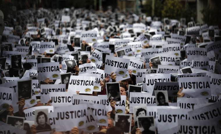 """Thousands of people hold up signs reading, """"Justice"""" as they gather to commemorate the 19th anniversary of the 1994 bombing of the Argentine Israeli Mutual Association (AMIA) Jewish community center in Buenos Aires. (Marcos Brindicci/Reuters photo)"""