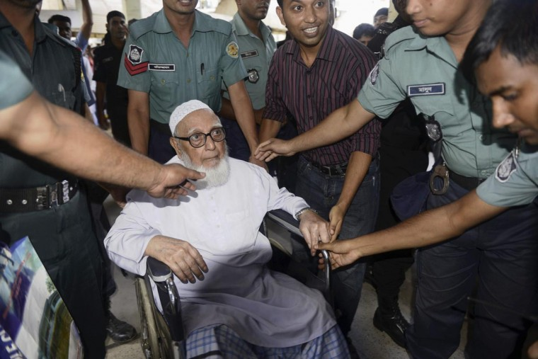 Ghulam Azam (C), former head of Jamaat-e-Islami party, exits a court after the verdict of his trial, in front of the International Crimes Tribunal-1 in Dhaka July 15, 2013. Bangladesh's war crimes tribunal convicted and sentenced Azam, 91, to life imprisonment on Monday, in the fifth such conviction since January, as violence broke out between police and his supporters across the country. Azam was found guilty on charges of planning, conspiracy, incitement and complicity to commit genocide and crimes against humanity during a 1971 war to break away from Pakistan, lawyers and tribunal officials said. (Stringer/Reuters)