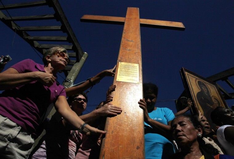 Faithfuls place their hands on the World Youth Day cross during a visit to the Vidigal slum in Rio de Janeiro July 15, 2013. Pope Francis will travel to Brazil on his first international trip as pontiff in July. (Pilar Olivares/Reuters)