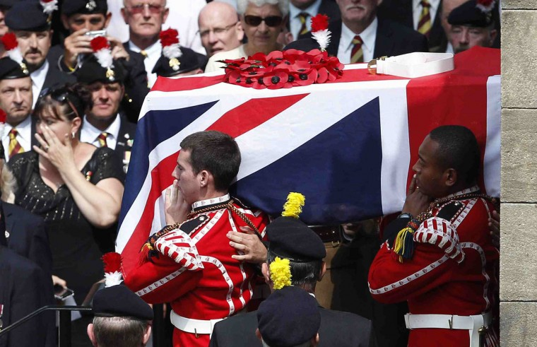 The coffin of Fusilier Lee Rigby is carried by members of his regiment after his funeral service at the parish church in Bury, northern England July 12, 2013. A British soldier who was hacked to death in London was buried on Friday, with Prime Minister David Cameron among the mourners paying their respects to an Afghanistan war veteran murdered on a busy street in broad daylight. (Dave Thompson/Pool/Reuters)