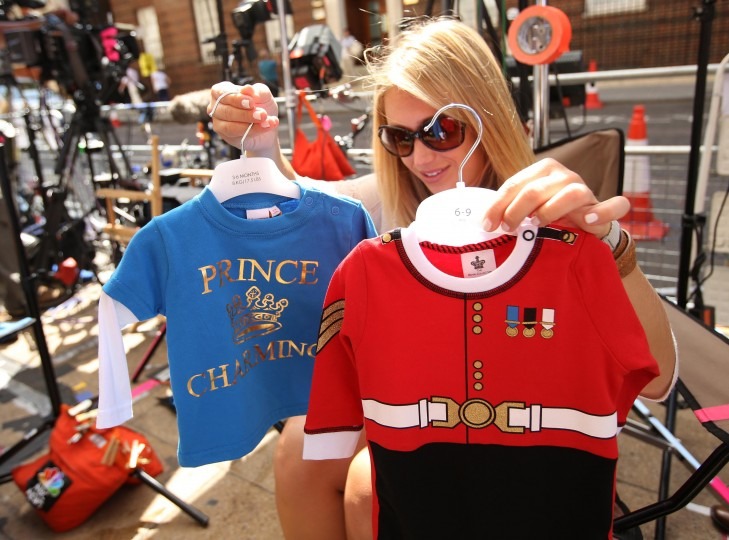A member of the U.S. media decides which baby clothes to show to the camera outside the Lindo Wing of St Mary's Hospital, where Britain's Catherine, Duchess of Cambridge is due to give birth, in London. (Olivia Harris/Reuters photo)